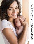pretty woman holding a newborn... | Shutterstock . vector #566789476