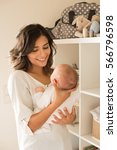 pretty woman holding a newborn... | Shutterstock . vector #566796598