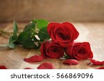 Stock photo three red roses and petals on old wood table with copy space romantic background 566869096
