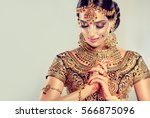 Portrait  smiling of beautiful indian girl. Young hindu woman model with golden kundan jewelry set . Traditional Indian costume lehenga choli .