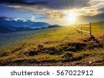 day and night transition time concept. wooden fence on grassy hillside near mountains with snowy peaks in spring - stock photo