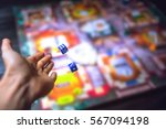 Small photo of Hand throws the dice on the background of colorful blurred fantasy Board games, gaming moments in dynamics