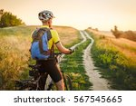 young man cycling on a rural... | Shutterstock . vector #567545665