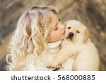 Stock photo little girl with a labrador puppy 568000885