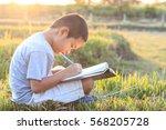 little asian boy writing book... | Shutterstock . vector #568205728