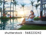 couple on the pool at tropical... | Shutterstock . vector #568223242