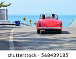 Stock photo couple in a red car on the road beside the sea 568439185