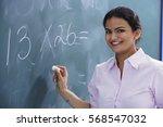 teacher smiling as she writes... | Shutterstock . vector #568547032