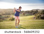 mature woman playing golf.... | Shutterstock . vector #568609252
