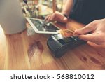 barista taking credit card to...   Shutterstock . vector #568810012
