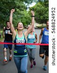 Small photo of Happy woman crossing the finish line with raised arms