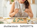 woman using pliers to adjust... | Shutterstock . vector #569039776