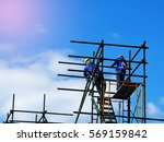 Construction workers working on scaffolding,Man Working on the Working at height with blue sky at construction site - stock photo