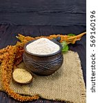Small photo of Flour amaranth in a clay cup, a spoon with grain, brown flower with green leaves on a napkin from a sacking on a background of dark wood planks