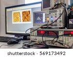 Small photo of digital oscilloscope on Desk with computer blurre