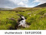 Small photo of Fluent river in green meadow in Scottish Highlands
