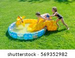 Small photo of An older sister tries to push her little brother down the slide into the blowup pool and water. Sibling fun.