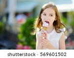 adorable little girl eating... | Shutterstock . vector #569601502