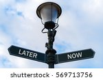 Small photo of Street lighting pole with two opposite directional arrows over blue cloudy background. Later versus Now concept.