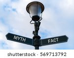 Small photo of Street lighting pole with two opposite directional arrows over blue cloudy background. Myth versus Fact concept.