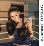Small photo of the girl on a ring boxes. She has very steady gaze. The girl has an eyebrow injury, but she is all the same ready to fight.