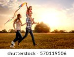 family running through field... | Shutterstock . vector #570119506