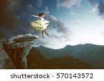 woman jumps from a high rock | Shutterstock . vector #570143572