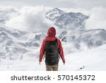 man in front of a snowy... | Shutterstock . vector #570145372