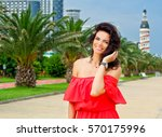 woman corrects hair and smile... | Shutterstock . vector #570175996
