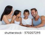 happy family in their bedroom... | Shutterstock . vector #570207295