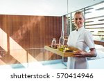 smiling masseuse holding a tray ... | Shutterstock . vector #570414946