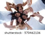 Small photo of Happy women forming a huddle against the sky