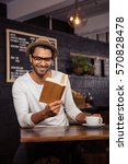man reading a book in a coffee... | Shutterstock . vector #570828478