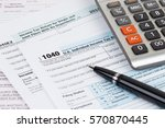 tax form with pen and calculator | Shutterstock . vector #570870445