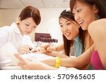 young women having their nails... | Shutterstock . vector #570965605