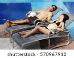 Couple Lying On Deck Chairs By...