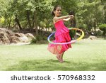 little girl playing with hula... | Shutterstock . vector #570968332