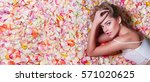 Stock photo valentine s day loving girl the girl in white dress lying on the floor in the petals of roses 571020625