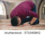muslim praying on the ground | Shutterstock . vector #571040842