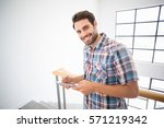 portrait of man holding digital ... | Shutterstock . vector #571219342