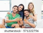 smiling friends sitting on sofa ... | Shutterstock . vector #571222756