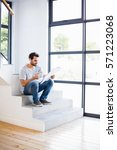 man on steps having cup of... | Shutterstock . vector #571223068