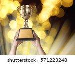 a man holding up a gold trophy... | Shutterstock . vector #571223248