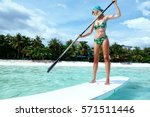 young woman paddling on sup... | Shutterstock . vector #571511446