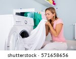 young woman smelling clean... | Shutterstock . vector #571658656