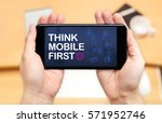 Small photo of Watching two hand holding mobile phone with Think mobile first word and feature icon with blur desk office background,Digital marketing.