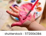 Child Painting Her Hand With...