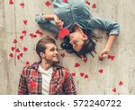 Stock photo top view of happy young couple looking at each other and smiling while lying on wooden floor girl 572240722