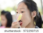 portrait of asian girl licking... | Shutterstock . vector #572250715