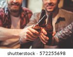 Stock photo cropped image of handsome friends clinking bottles of beer and smiling while resting at the pub 572255698